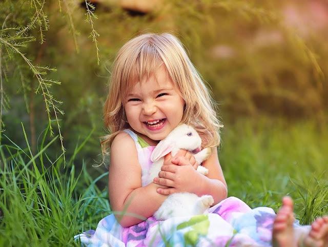 vajzë e bogël duke qeshur dhe përqafuar një lepur