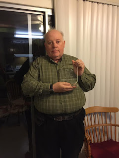 William stands beside window holding CMAC Producer of the year 2017 award in his left hand.