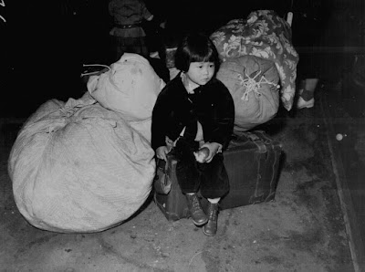 Clem Albers, A young evacuee of Japanese ancestry waits with the family baggage before leaving by bus for an assembly center, April 1942. Courtesy National Archives