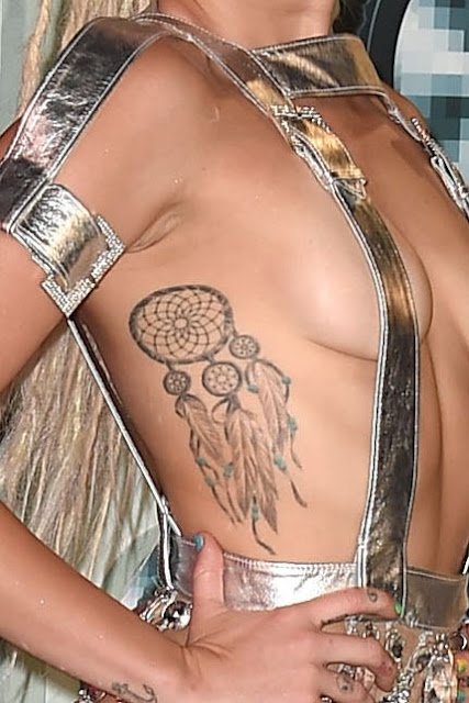Miley Cyrus dream catcher tattoo on the right side of her rib cage under her arm