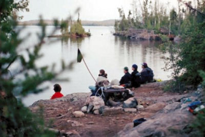 campers sitting by a lake