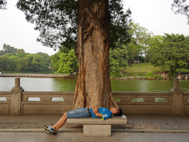 man sleeping on a stone bench at Zhongshan Park in Foshan