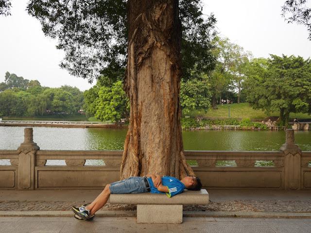 man sleeping on a stone bench at Zhongshan Park in Foshan