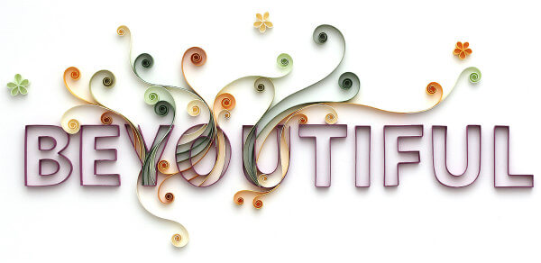 Quilled paper word BEYOUTIFUL with decorative paper scrolls and tiny quilled flowers