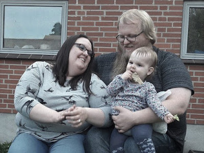 Me, my husband and daughter together outdoors laughing.