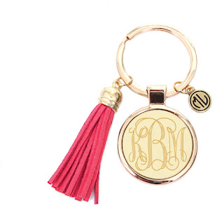 White Background Image of Gold Keychain With Pink Tassel