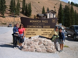 Four ladies with their hiking gear on, taking a photo at the Continental Divide sign on Monarch Pass.
