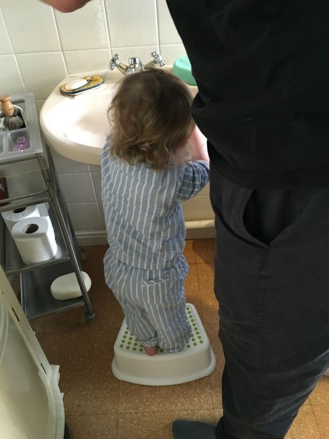 toddler stood on stool next to sink