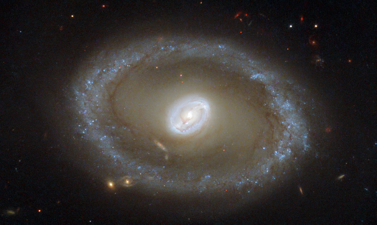 "Hubble Eyes Golden Rings of Star Formation Hubble Eyes Golden Rings of Star Formation    Taking center stage in this new NASA/ESA Hubble Space Telescope image is a galaxy known as NGC 3081, set against an assortment of glittering galaxies in the distance. Located in the constellation of Hydra (The Sea Serpent), NGC 3081 is located over 86 million light-years from us. It is known as a type II Seyfert galaxy, characterized by its dazzling nucleus.  NGC 3081 is seen here nearly face-on. Compared to other spiral galaxies, it looks a little different. The galaxy's barred spiral center is surrounded by a bright loop known as a resonance ring. This ring is full of bright clusters and bursts of new star formation, and frames the supermassive black hole thought to be lurking within NGC 3081 — which glows brightly as it hungrily gobbles up in-falling material.  These rings form in particular locations known as resonances, where gravitational effects throughout a galaxy cause gas to pile up and accumulate in certain positions. These can be caused by the presence of a ""bar"" within the galaxy, as with NGC 3081, or by interactions with other nearby objects. It is not unusual for rings like this to be seen in barred galaxies, as the bars are very effective at gathering gas into these resonance regions, causing pile-ups which lead to active and very well-organized star formation.  Hubble snapped this magnificent face-on image of the galaxy using the Wide Field Planetary Camera 2. This image is made up of a combination of ultraviolet, optical, and infrared observations, allowing distinctive features of the galaxy to be observed across a wide range of wavelengths.  Image credit: ESA/Hubble & NASA; acknowledgement: R. Buta (University of Alabama) Explanation from: http://www.nasa.gov/content/goddard/hubble-eyes-golden-rings-of-star-formation/"