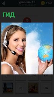 Девушка с наушниками и микрофоном в руках держит маленький глобус, изображая гида