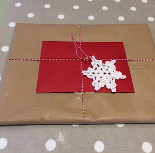 Parcel wrapped in brown paper, topped with a crochet snowflake
