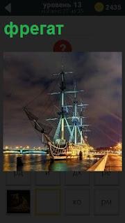 На рейде в порту стоит освещенный фрегат, у которого спущены паруса и подсветка с низу