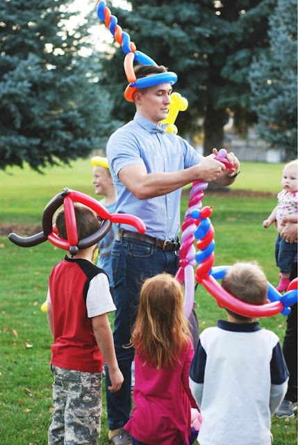 The Utah Balloon Artist making balloon animals for some kids at a park