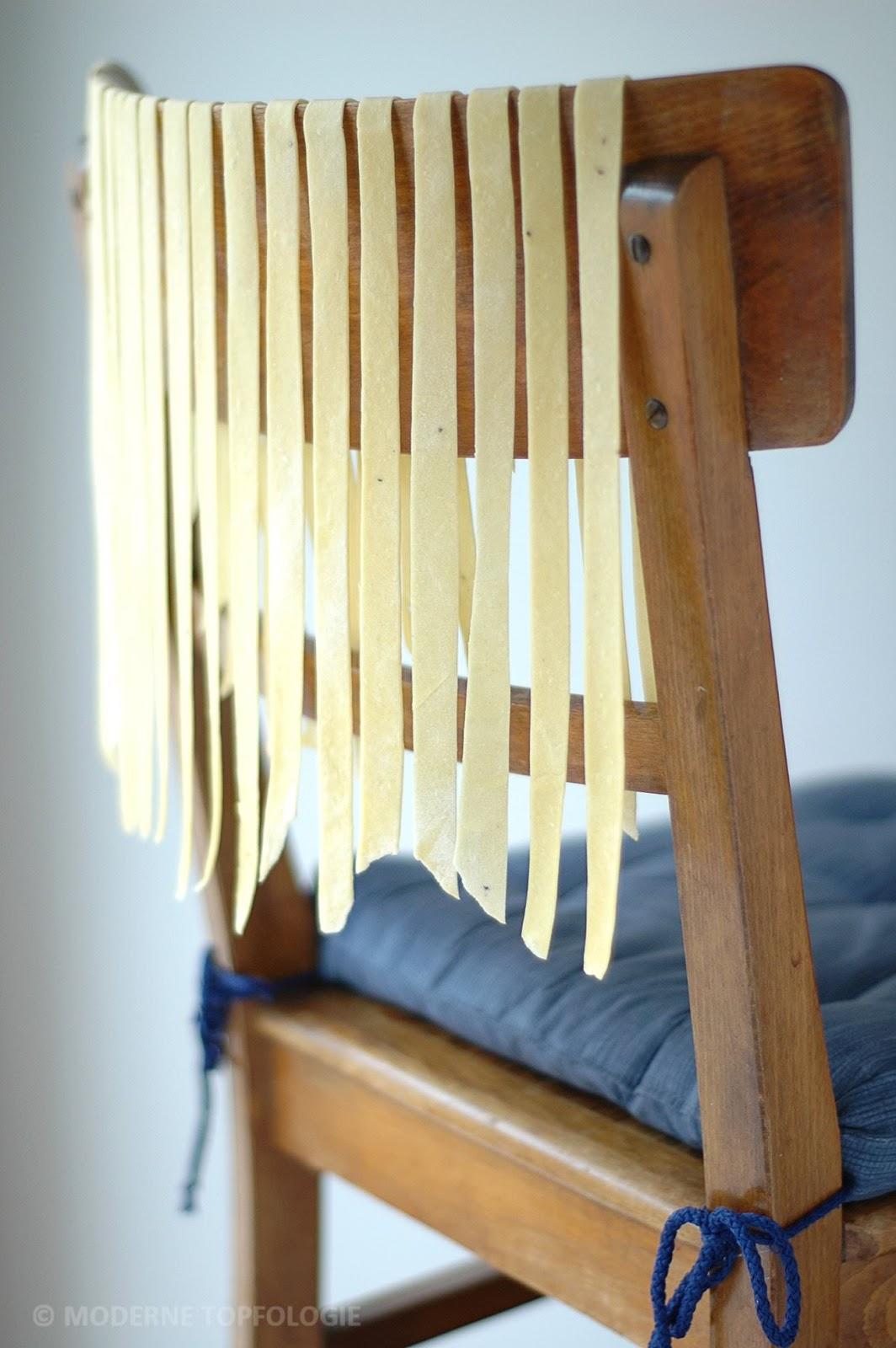 Frisch zubereitete Nudeln haengen zum Trocknen auf einer Stuhllehne