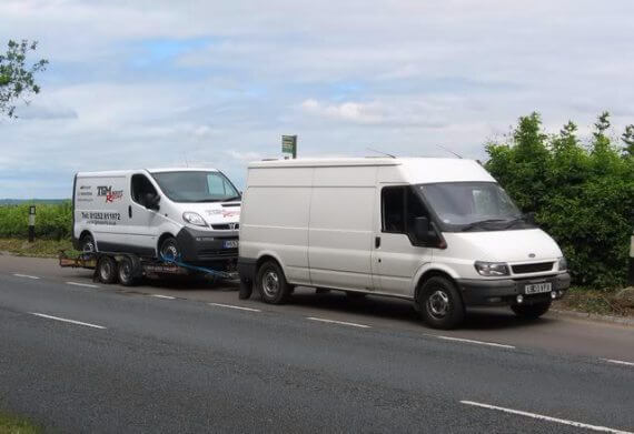 One white Ford Transit is towing another