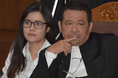 Jessica Wongso sits in court next to her lawyer