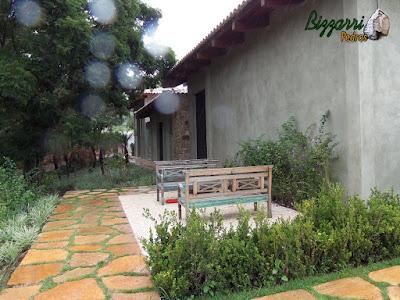 Execução do caminho no jardim com pedra Goiás com a praça com piso de pedrisco palha com os bancos de madeira e a execução do paisagismo em residência em Piracaia-SP.