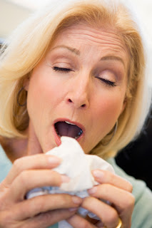 Photo of a Middle-Aged Woman Sneezing into a Kleenex