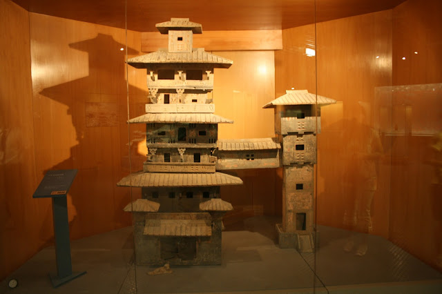 A Chinese Eastern-Han Dynasty (25–220 AD) ceramic model of a multistory manor house with a covered bridge extended to a smaller watchtower