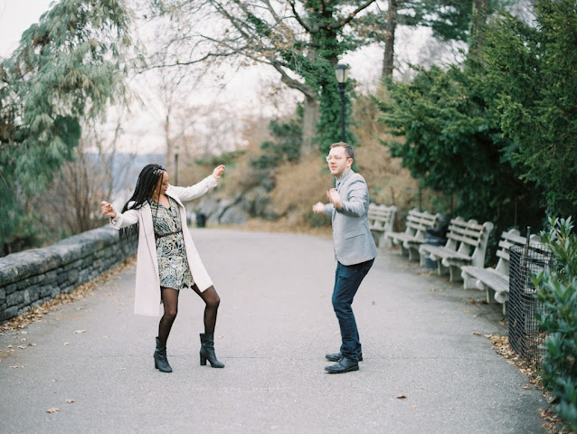 engaged couple dancing in park