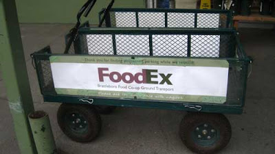 Green garden cart with a sign on the side that says FoodEx, mimicing the FederalEx logo