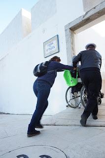 Uma auxiliar e um faroleiro ajudam um aluno em cadeira de rodas a subir uma rampa íngreme