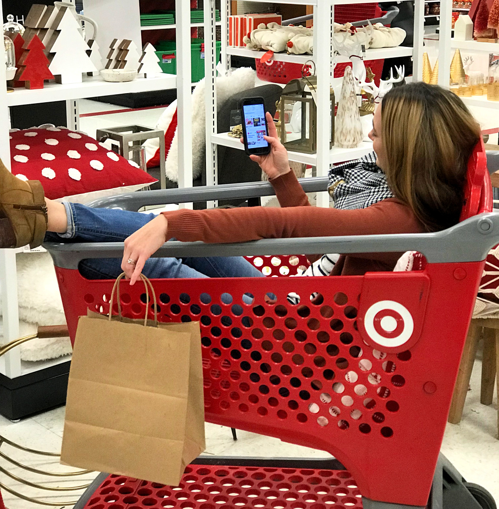 sitting in a Target shopping cart doing holiday shopping