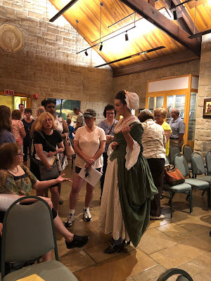 Jessica Young in 18th century clothing talks with Bushy Run visitors