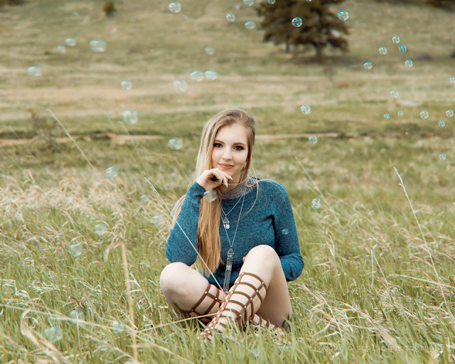 a girl poses in a meadow with bubbles for her senior portraits in Boulder Colorado