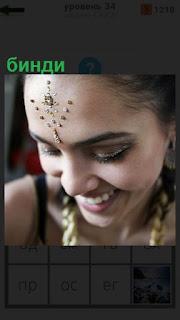 имеется бинди на голове у женщины с украшениями