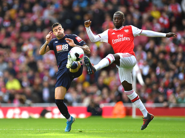Nicolas Pepe of Arsenal is challenged by Diego Rico of AFC Bournemouth during the Premier League match between Arsenal FC and AFC Bournemouth at Emirates Stadium on October 06, 2019 in London, United Kingdom
