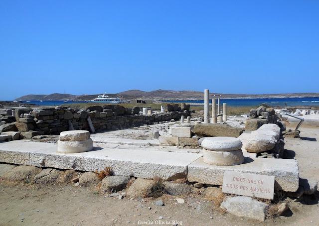 ruiny zabytkowej świątyni Naksyjczyków, kolumny i bloki marmurowe na tle błękitengo morza i nieba Delos Grecja