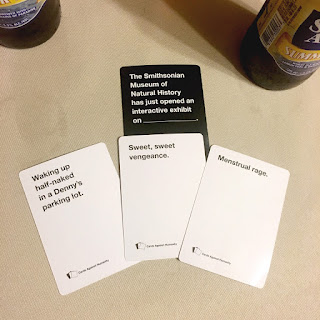 """Image: four game cards on a table, reading, """"The Smithsonian Museum of Natural History has just opened an interactive exhibit on ______"""" and three potential responses."""