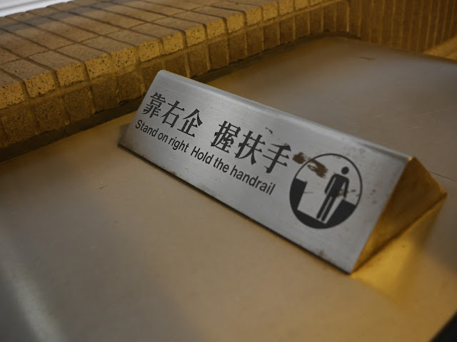 'Stand on right — Hold the handrail' sign on an escalator in Hong Kong