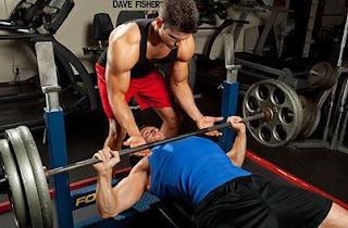 pareja fitness haciendo press banca con barra