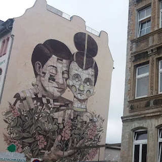 Foto de uma parede lateral de um prédio na Alemanha com um grafite de Pixel Pancho, muralista italiano, de Turim. Pancho mistura o orgânico-mecânico com exatidão nos traços e uma sutil fantasia. Descrição: Parede em fundo bege, ao centro, um casal da cintura para cima. O homem à esquerda, está logo atrás de uma mulher, ele encosta o rosto junto ao dela e o peito nas costas da mulher. Ela tem aparência robótica, rosto oval feito de placas e cabelos escuros presos em coque alto; os olhos redondos e profundos tem aspecto de um vórtice mecânico, o nariz é um pequeno sino, em cada bochecha, um respiro redondo telado, os pequenos lábios são finos sem expressão, no pescoço, uma gargantilha verde claro no mesmo tom do nariz. Ele tem traços humanos, cabelos da mesma cor,  rosto oval, sobrancelhas finas, nariz pontudo, lábios médios e um parafuso na lateral do pescoço ; o rosto é composto por pequenas placas diferentes da mulher, que encaixam-se; algumas, estão abertas, de onde brotam pequenas mudas de plantas; o mesmo acontece com a parte do peito repleto de cachos com flores em rosa claro e folhas cinzas. O homem coloca a mão esquerda em concha entremeada pelas ramas e flores, à frente do peito da mulher, onde algumas engrenagens circulares estão a mostra, semi ocultas pelo florido buquê. Um fino ramo com brotos na extremidade, sobe e delineia o ombro direito da mulher robô. Na lateral direita, parte da fachada de outro prédio em tijolos aparentes.