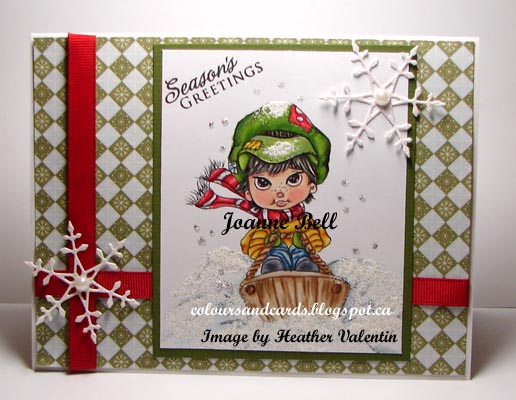 Christmas card with boy wearing green hat and red scarf on sled