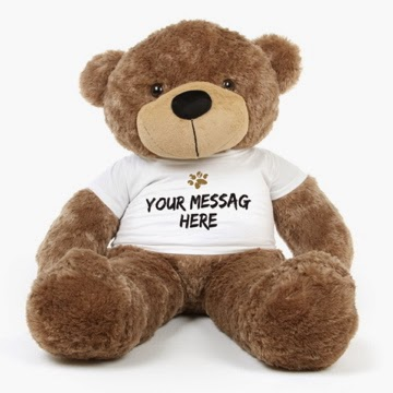 48in Personalized Sunny Cuddles teddy bear in a Paw Print shirt with your message on the front