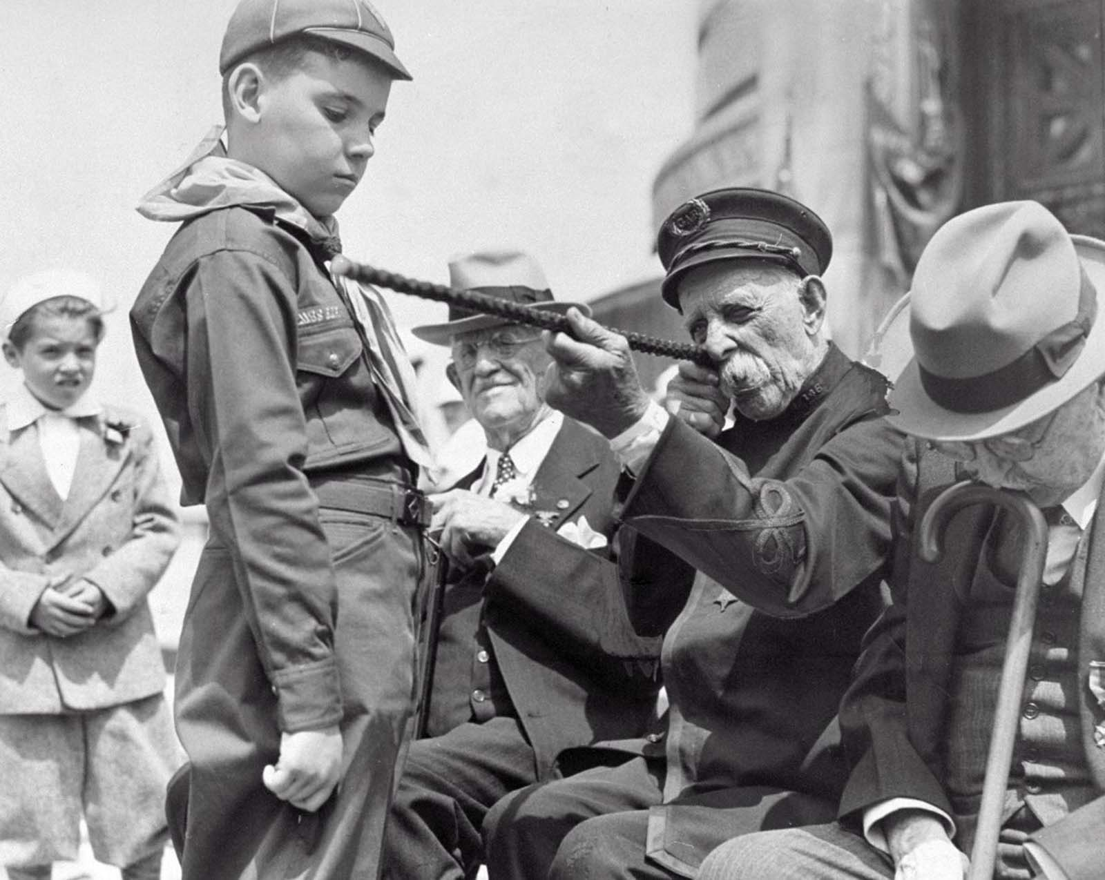 At the Memorial Day parade, Civil War veteran, George W. Collier, 97, shows Alwin Sharr, 9, a boy scout cub, how he aimed his rifle during the war. 1939.