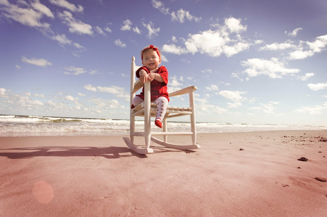 A baby sits in a rocking chair at the beach in Florida.