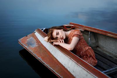 Linda chica con cabeza apoyada en pequeño barco mirando a cámara