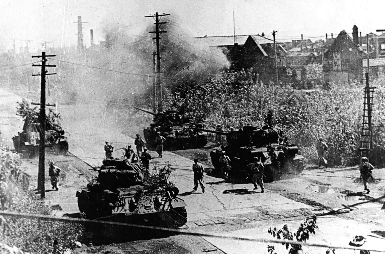 In this undated photo from North Korea's official Korean Central News Agency, distributed by Korea News Service, North Korean combatants plunge together with the tank unit in Seoul during the Korean War.