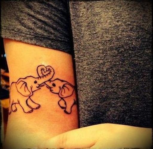 Um par de elefantes moldar seus troncos em forma de coração em preto tatuagem.