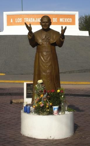 Foto a la estatua de Juan Pablo II acompañado de flores