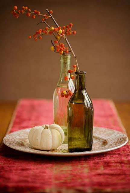 pretty fall decoration with orange berries, branches and bottles