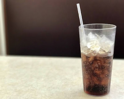 carbonated cola drink in a glass with ice and a straw