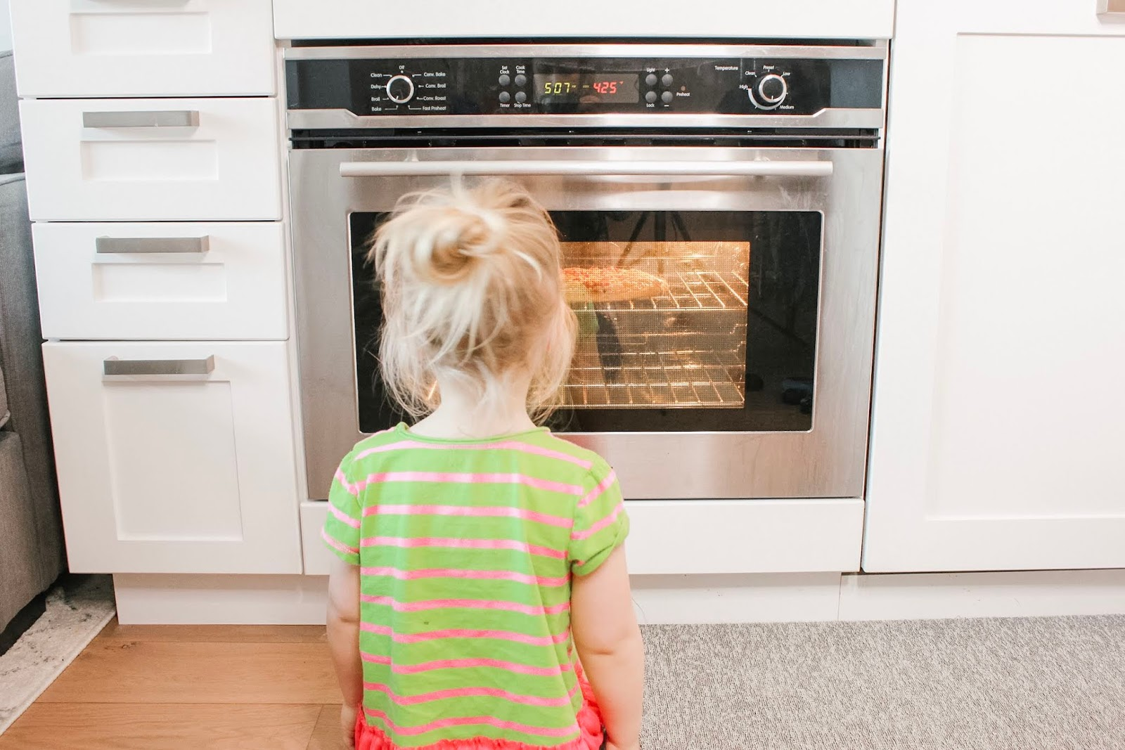 toddler sitting in front of oven waiting for pizza