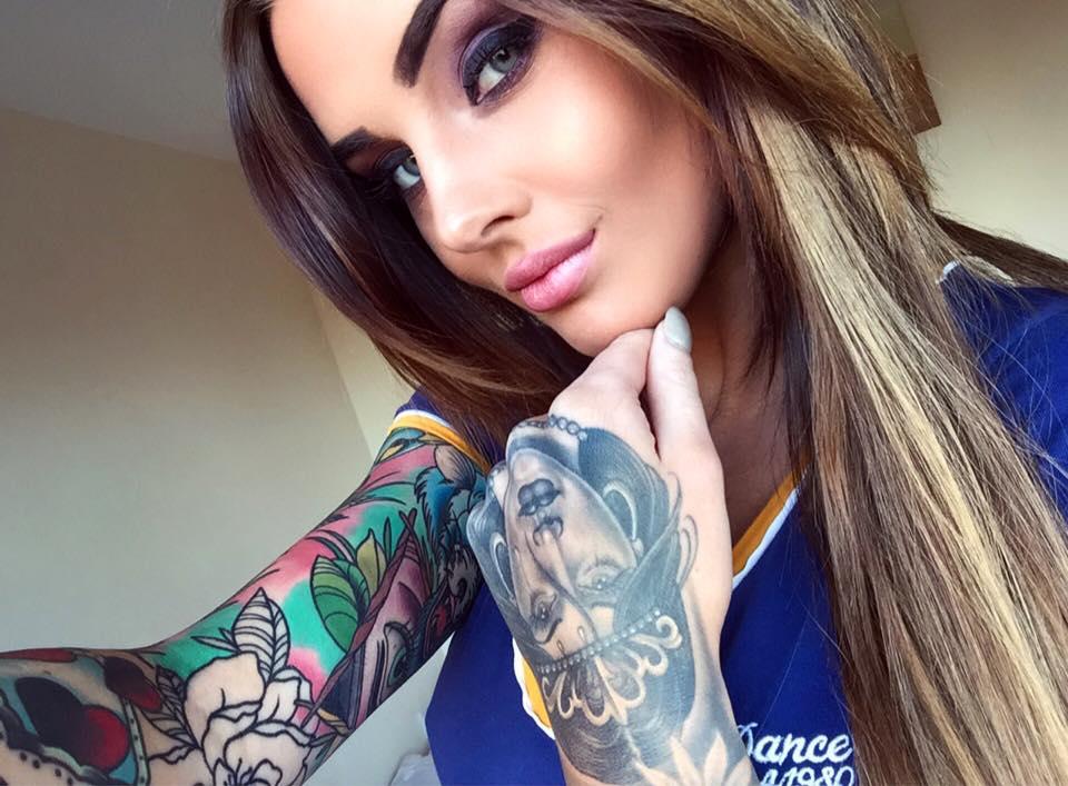 Impresionante chica modelo de ojos verdes, nos mira mientras se saca una foto, lleva tatuajes a todo color en los brazos