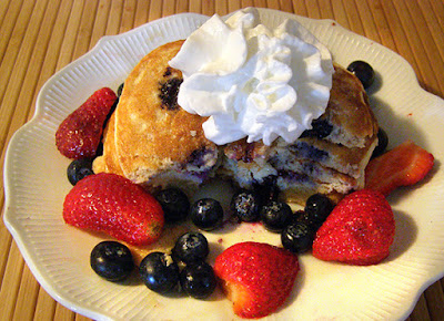Blueberry Pancakes garnished with blueberries, strawberries, and whipped cream