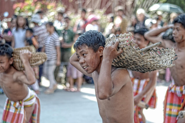 Young Boy Indigenous Street Dancer Carrying Heavy River Stone Woven Fish Catcher